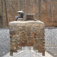 Brick Mason repairing a Chimney Top on a Roof