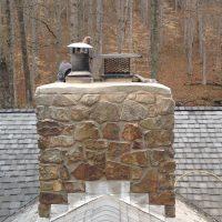 Brick Mason repairing a Chimney Top on a Roof